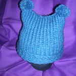 blue knit hat with pompoms - back view